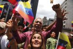 Supporters of Venezuelan President Nicolas Maduro wave Venezuelan flags outside of the National Assembly during the swearing in ceremony of the Constituents Assembly, in Caracas, Venezuela, Friday, Aug. 4, 2017. Venezuelan President Nicolas Maduro is heading toward a showdown with his political foes, after seating a loyalist assembly that will rewrite the country's constitution and hold powers that override all other government branches.(AP Photo/Wil Riera)